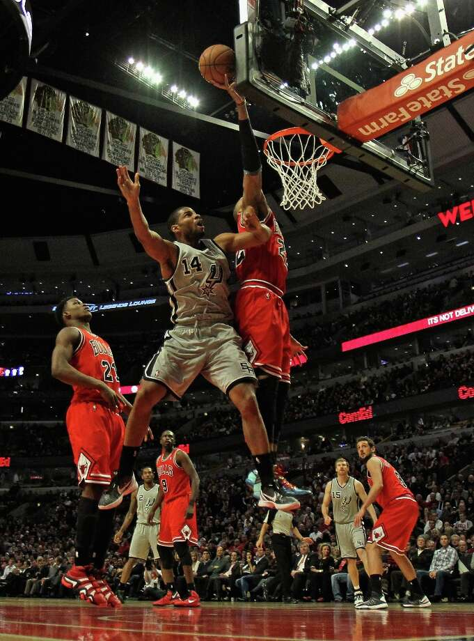 Taj Gibson #22 of the Chicago Bulls blocks a shot by Gary Neal #14 of the Spurs at the United Center on Feb. 11, 2013 in Chicago. The Spurs defeated the Bulls 103-89. Photo: Jonathan Daniel, Getty Images / 2013 Getty Images