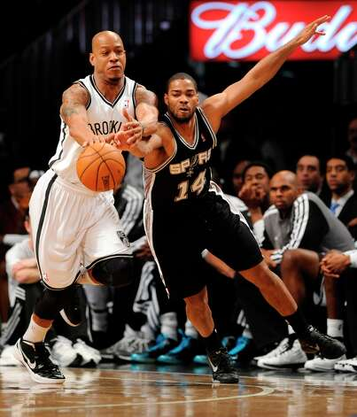 The Spurs' Gary Neal (14) and Brooklyn Nets' Keith Bogans (10) scramble for a loose ball in the first half on Sunday, Feb., 10, 2013 at Barclays Center in New York. Photo: Kathy Kmonicek, Associated Press / FR170189 AP