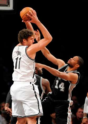 Brooklyn Nets center Brook Lopez (11) looks to pass over Spurs guard Gary Neal (14) on Sunday, Feb., 10, 2013 at Barclays Center in New York. Photo: Kathy Kmonicek, Associated Press / FR170189 AP