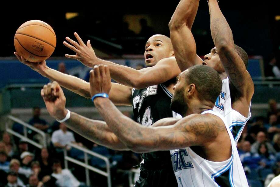 The Spurs' Gary Neal, left, gets around Orlando Magic's Kyle O'Quinn, center, and DeQuan Jones, right, for a basket during the second half Wednesday, Nov. 28, 2012, in Orlando, Fla. The Spurs won 110-89. Photo: John Raoux, Associated Press / AP