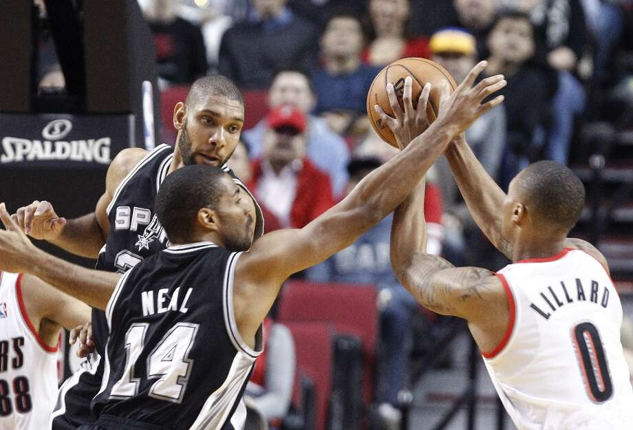 Portland Trail Blazers guard Damian Lillard, right, is double-teamed by the Spurs' Gary Neal (14) and Tim Duncan during the first quarter in Portland, Ore., Thursday, Dec. 13, 2012. Photo: Don Ryan, Associated Press / AP
