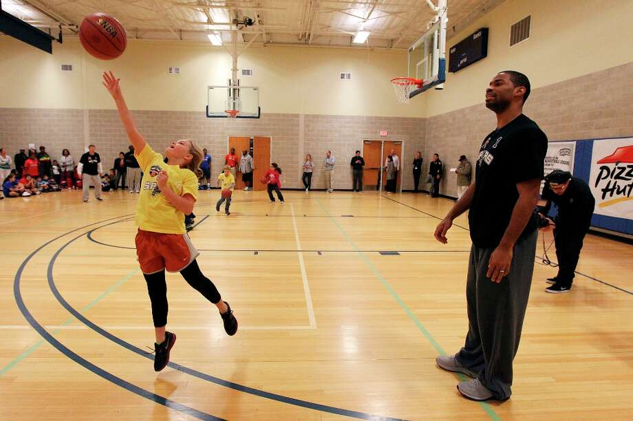 Spurs' guard Gary Neal (right) watches Jordan Salisbury, 9, take a shot at the basket during the Spurs Youth Basketball League Kids Clinic at the Walzem YMCA on Tuesday, Jan. 15, 2013. About a hundred kids came out to interact with Neal and Spurs Assistant Coach Brett Brown. The clinic stressed the importance of making good decisions and staying in school while also teaching the kids a few basketball fundamentals. Photo: Kin Man Hui, San Antonio Express-News / © 2012 San Antonio Express-News