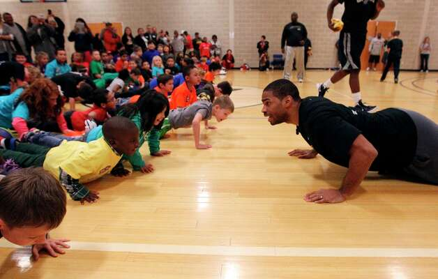 Spurs' guard Gary Neal (right) does push-ups with kids at the Spurs Youth Basketball League Kids Clinic at the Walzem YMCA on Tuesday, Jan. 15, 2013. About a hundred kids came out to interact with Neal and Spurs Assistant Coach Brett Brown. The clinic stressed the importance of making good decisions and staying in school while also teaching the kids a few basketball fundamentals. Photo: Kin Man Hui, San Antonio Express-News / © 2012 San Antonio Express-News
