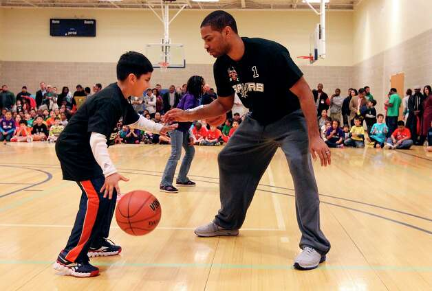 Spurs' guard Gary Neal helps Oscar Gonzalez, 8, with a drill at the Spurs Youth Basketball League Kids Clinic at the Walzem YMCA on Tuesday, Jan. 15, 2013. About a hundred kids came out to interact with Neal and Spurs Assistant Coach Brett Brown. The clinic stressed the importance of making good decisions and staying in school while also teaching the kids a few basketball fundamentals. Photo: Kin Man Hui, San Antonio Express-News / © 2012 San Antonio Express-News