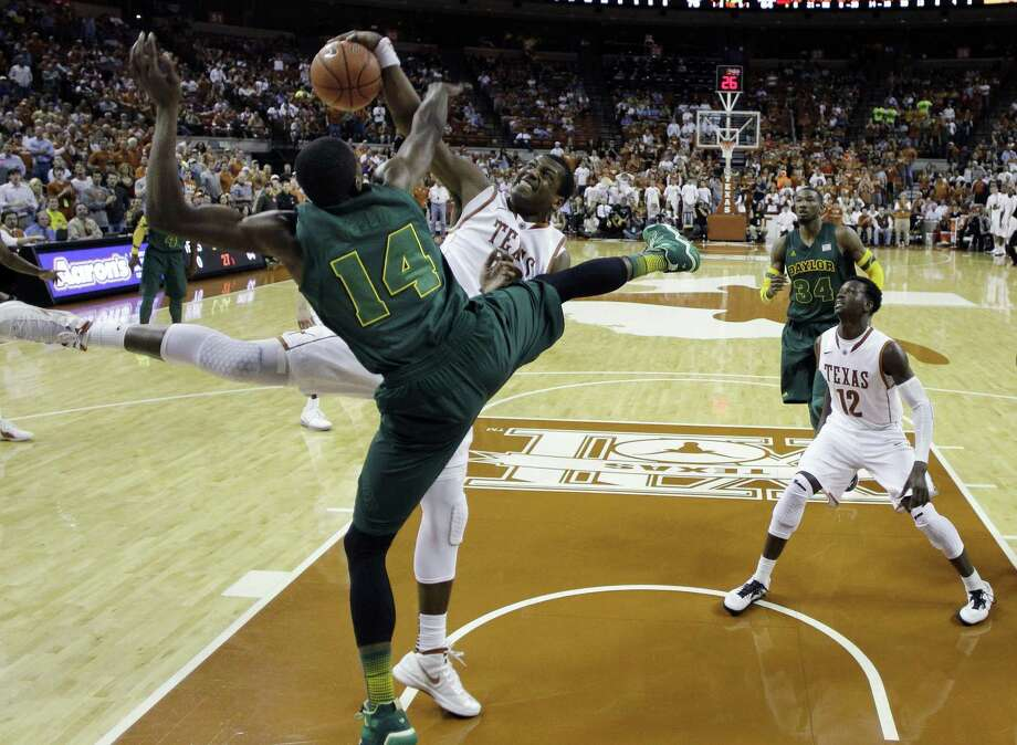 UT's Jonathan Holmes (center) fouls Baylor's Deuce Bello (14) as he tries to block his shot.