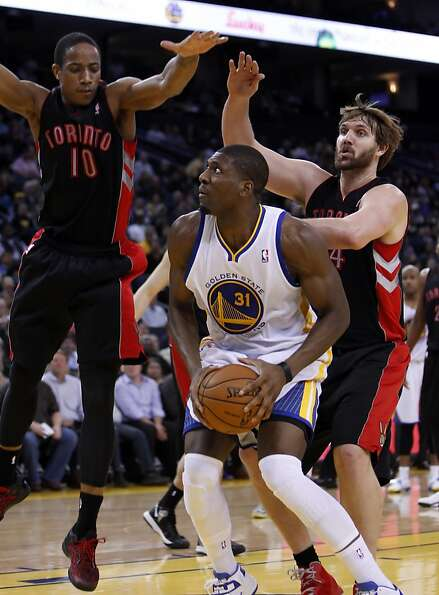 Festus Ezeli (31) is guarded under the basket by Toronto's Aaron Gray, (34), right, and Demar DeRoza