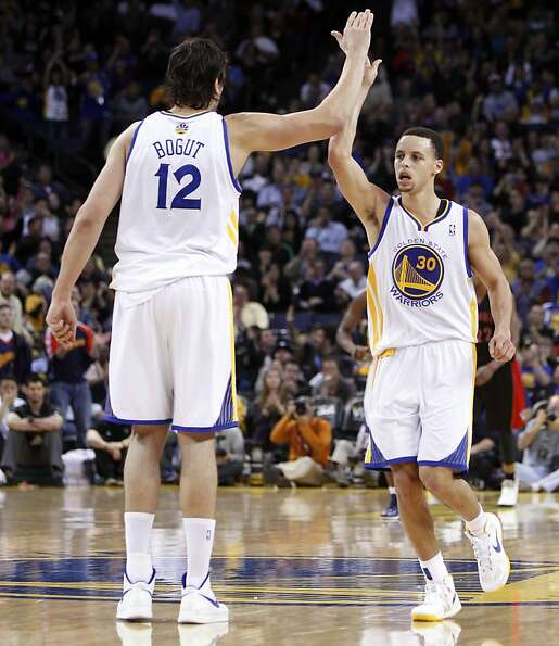 Back in the lineup, Andrew Bogut congratulates Stephen Curry after Curry hit a three-pointer in the