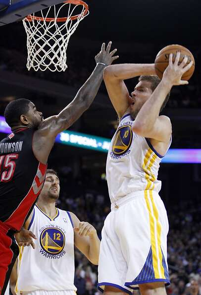 David Lee (10) pulls in a rebound and is fouled by Toronto's Amir Johnson (15) in the second half. T