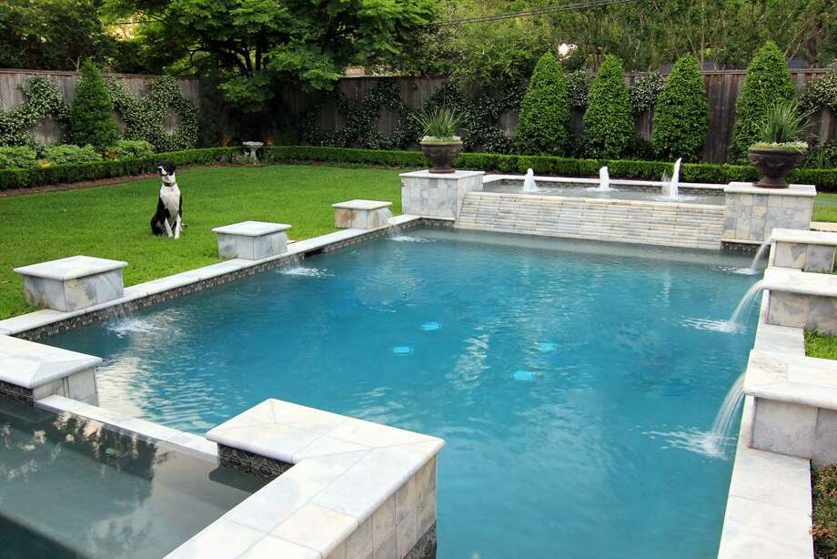 Another view of the back yard pool - this one more closely showing the unique design of the pool with fountain in the distance and marble coping around pool/hot tub. A relaxing spot to enjoy being outdoors. Photo: Martha Turner Properties