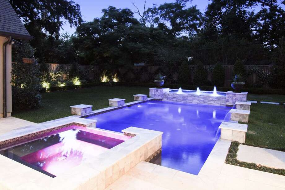 A closer view of the night lighting illuminating the backyard perimeter landscaping and the pool/hot tub/fountains. Photo: Martha Turner Properties