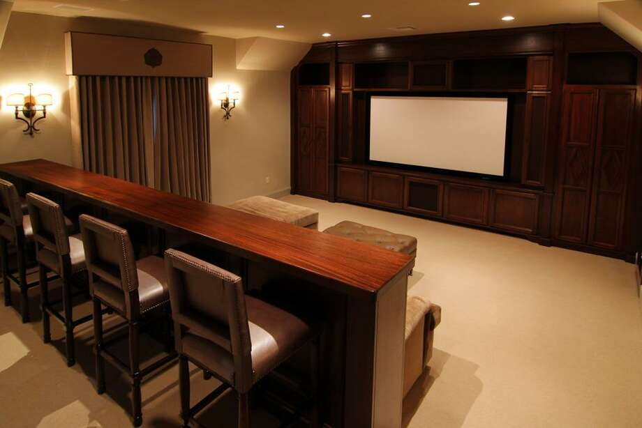 The upstairs media room (21 x 17) is cleverly designed to include a handsome wood stained entertainment center, spacious seating area and elevated seating behind a stained wood bar stand. Photo: Martha Turner Properties