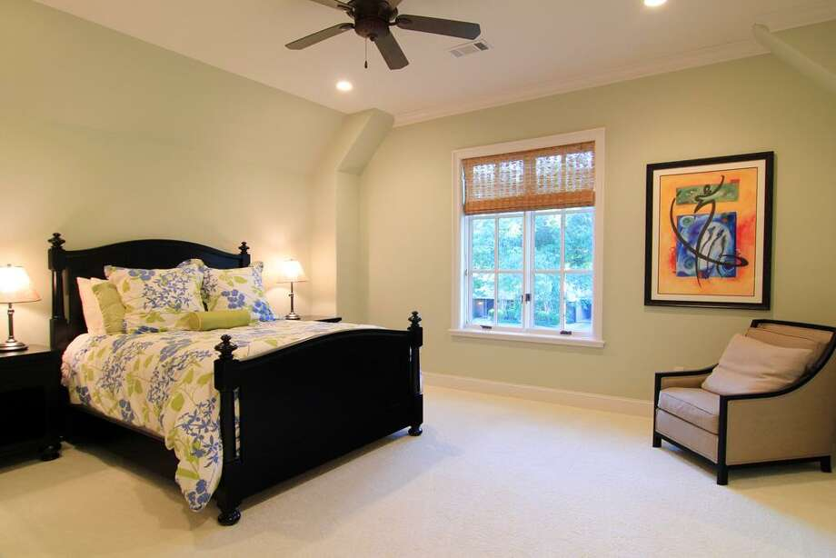 The second of three upstairs guest bedrooms - this one with recessed lighting, mullioned window with roman shades, carpeted flooring, ceiling fan, walk-in closet with shelving and en suite bath. Photo: Martha Turner Properties