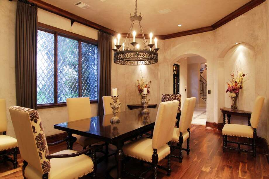 The impressive dining room (17 x 14) includes faux painted walls, walnut flooring, wood stained crown/base molding, series of three leaded glass windows with draperies, elegant chandelier, art niches and surround sound. Photo: Martha Turner Properties