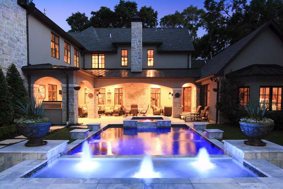 A night view of the backyard showing off the great mood setting lighting installed throughout the backyard landscaping and pool/hot tub/fountain and covered outdoor living/dinning areas. Photo: Martha Turner Properties