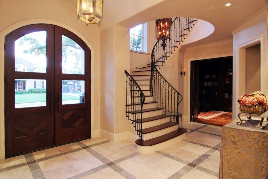 Exquisite describes the front entry (12 x 25) with Jerusalem stone flooring/decorative insets, faux painted walls, barrel vaulted ceiling, double entry doors with glass fronts, circular staircase with wrought iron railing/wood treads/painted risers. Photo: Martha Turner Properties