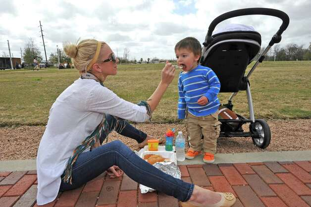 Kristin Davis, left, using the sidewalk next to the Great Lawn, gives a sample of boudain to her nephew Knox Adams, right, who was walking up and down on the bricks.  The downtown Lunch on the Lake event, held at the Beaumont Event Centre in downtown Beaumont, started again this year on Monday March 4, 2013.  The vendors have moved to the street area directly adjacent to the Great Lawn, not by the lake like they were last year. Dave Ryan/The Enterprise