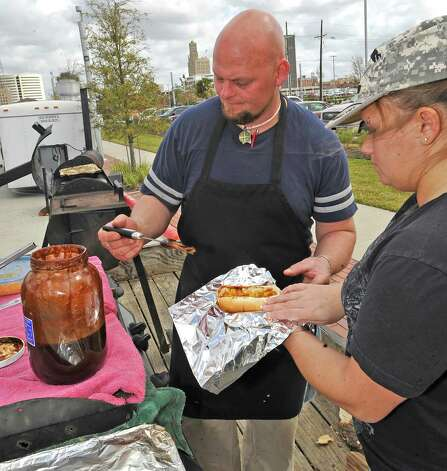 Brent Wise, left, of the Wise Guy Grill booth, puts his secret sauce on another order held by Karla Harrington, right. The downtown Lunch on the Lake event, held at the Beaumont Event Centre in downtown Beaumont, started again this year on Monday March 4, 2013.  The vendors have moved to the street area directly adjacent to the Great Lawn, not by the lake like they were last year. Dave Ryan/The Enterprise