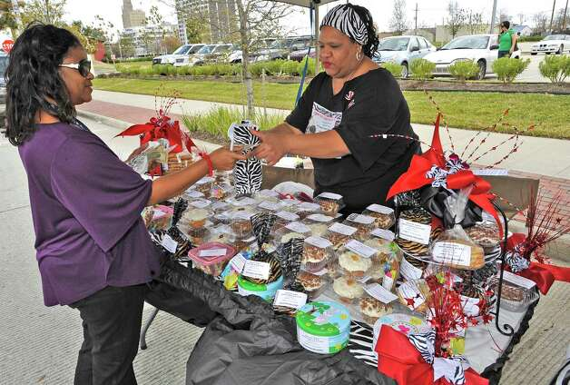 Anita Brown, left, buys desert at the Granny Flo's Sweet Treats & Eats booth, from Janice Solomon, right. The downtown Lunch on the Lake event, held at the Beaumont Event Centre in downtown Beaumont, started again this year on Monday March 4, 2013.  The vendors have moved to the street area directly adjacent to the Great Lawn, not by the lake like they were last year. Dave Ryan/The Enterprise