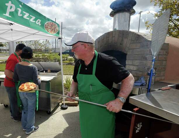 Jim Robichau, brings another brick oven pizza out of the oven behind him for a customer.  Divina La Pizza was at the event for the first time.   The downtown Lunch on the Lake event, held at the Beaumont Event Centre in downtown Beaumont, started again this year on Monday March 4, 2013.  The vendors have moved to the street area directly adjacent to the Great Lawn, not by the lake like they were last year. Dave Ryan/The Enterprise