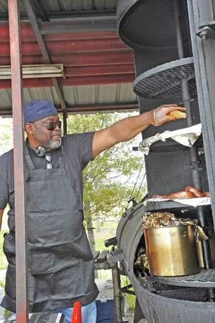 Over at the Big Bo's BBQ and Mama's Soul Food Booth, John McZeal readies another lunch as he grabs part of it from his big pit outside.  The downtown Lunch on the Lake event, held at the Beaumont Event Centre in downtown Beaumont, started again this year on Monday March 4, 2013.  The vendors have moved to the street area directly adjacent to the Great Lawn, not by the lake like they were last year. Dave Ryan/The Enterprise