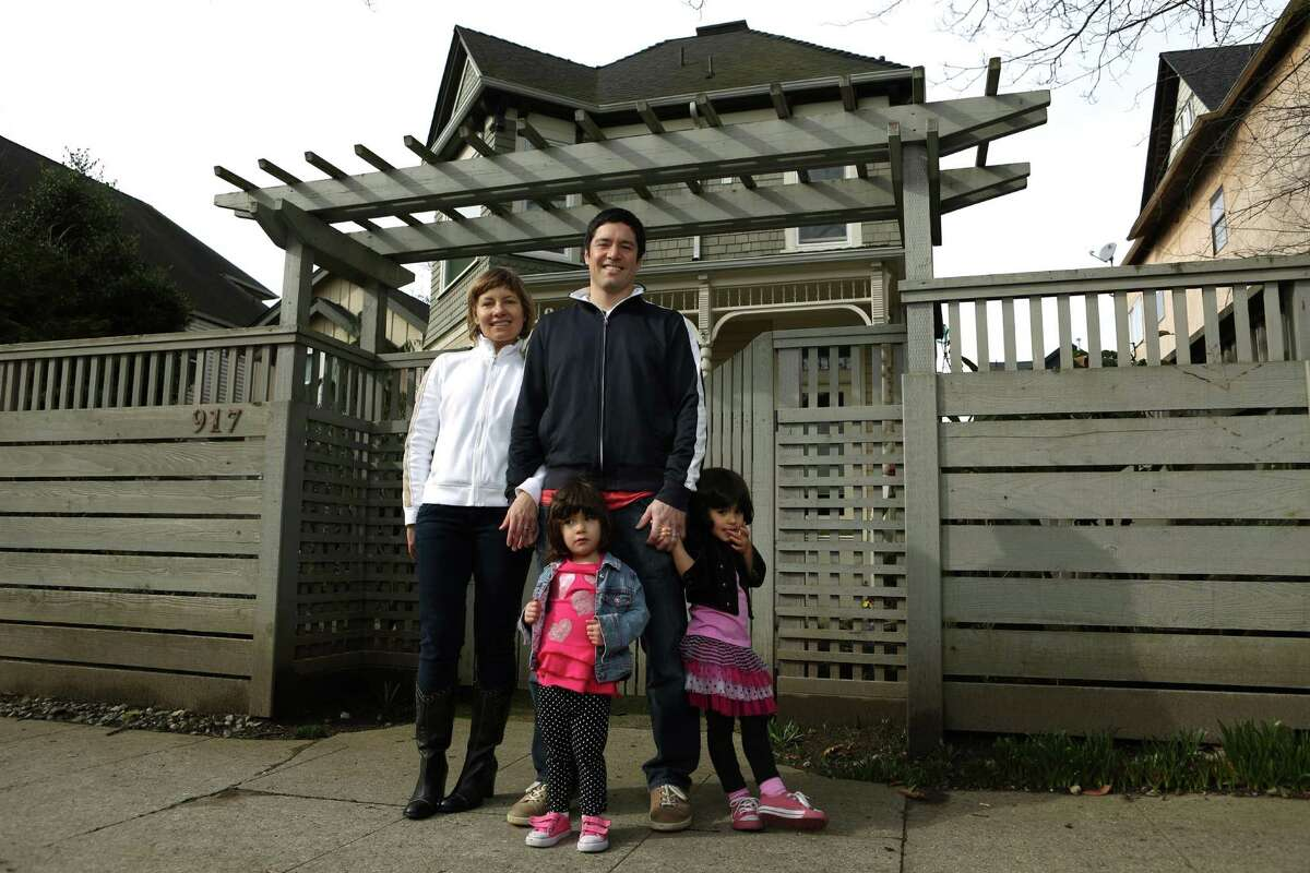 Ana and John Griffin are shown with their daughters Andalia, 2, left, and Tesora, 3, in front of their new home on Saturday, March 2, 2013. The family wrote a 'love letter' about the house, helping seal the deal with the seller as the real estate market continues to pick up.