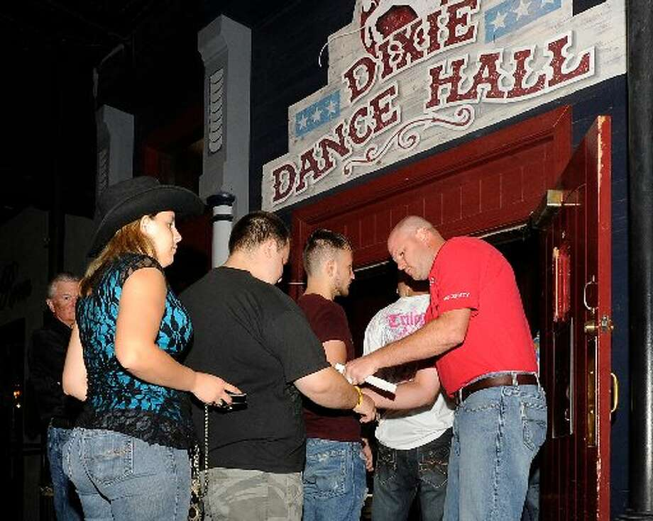 Doorman Jeremy Faulk, right, checks ID's and issues wristbands as patrons enter the Dixie Dance Hall on Crockett Street. Valentino Mauricio/cat5