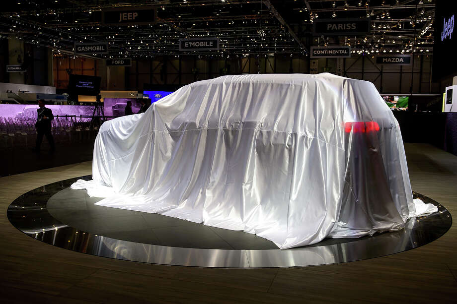 A car is waiting to be unveiled at the Jeep booth during the 83rd Geneva Motor Show on March 5, 2013 in Geneva.  The Geneva International Motor Show opened its doors to the press under a dark cloud, with no sign of a speedy rebound in sight for the troubled European market. The event, which is considered one of the most important car shows of the year, will again be heavily marked by the crisis in Europe after an already catastrophic year in 2012. Photo: FABRICE COFFRINI, AFP/Getty Images / 2013 AFP
