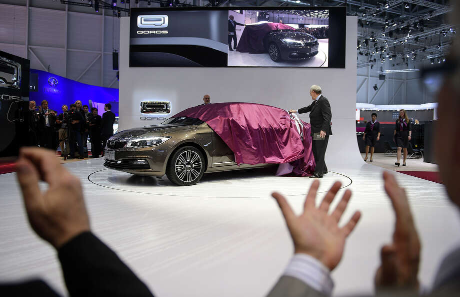 A Qoros 3 Sedan is unveiled as an European premiere at the Chinese car maker's booth during the 83rd Geneva Motor Show on March 5, 2013 in Geneva. The Geneva International Motor Show opens its doors under a dark cloud, with no sign of a speedy rebound in sight for the troubled European market. Photo: FABRICE COFFRINI, AFP/Getty Images / 2013 AFP