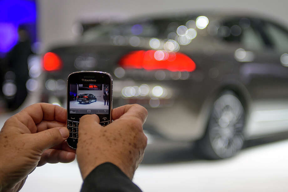 A visitor snaps a picture of the Qoros 3 Sedan unveiled as an European premiere at the Chinese car maker's booth during the 83rd Geneva Motor Show on March 5, 2013 in Geneva. The Geneva International Motor Show opens its doors under a dark cloud, with no sign of a speedy rebound in sight for the troubled European market. Photo: FABRICE COFFRINI, AFP/Getty Images / 2013 AFP