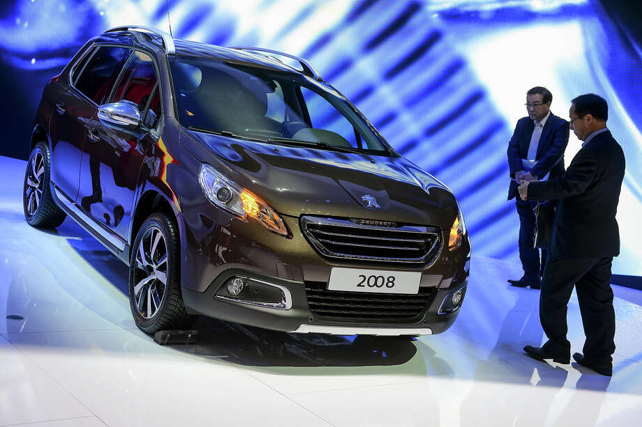 The new Peugeot 2008 is displayed as World premiere at French car maker's booth during the 83rd Geneva Motor Show on March 5, 2013. The Geneva International Motor Show opens its doors under a dark cloud, with no sign of a speedy rebound in sight for the troubled European market. Photo: FABRICE COFFRINI, AFP/Getty Images / 2013 AFP