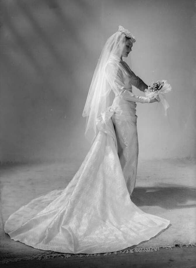 1948:A model bride in a slim line wedding dress with bustle and train wears a floral headdress. The high  fastening, hip length bodice has long sleeves and pearl buttons. Photo: Chaloner Woods, Getty / Hulton Archive