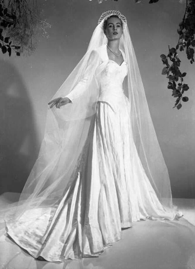 1951:A satin wedding dress by Mercia with a long veil held in position by a tiara. Photo: Chaloner Woods, Getty / Hulton Archive