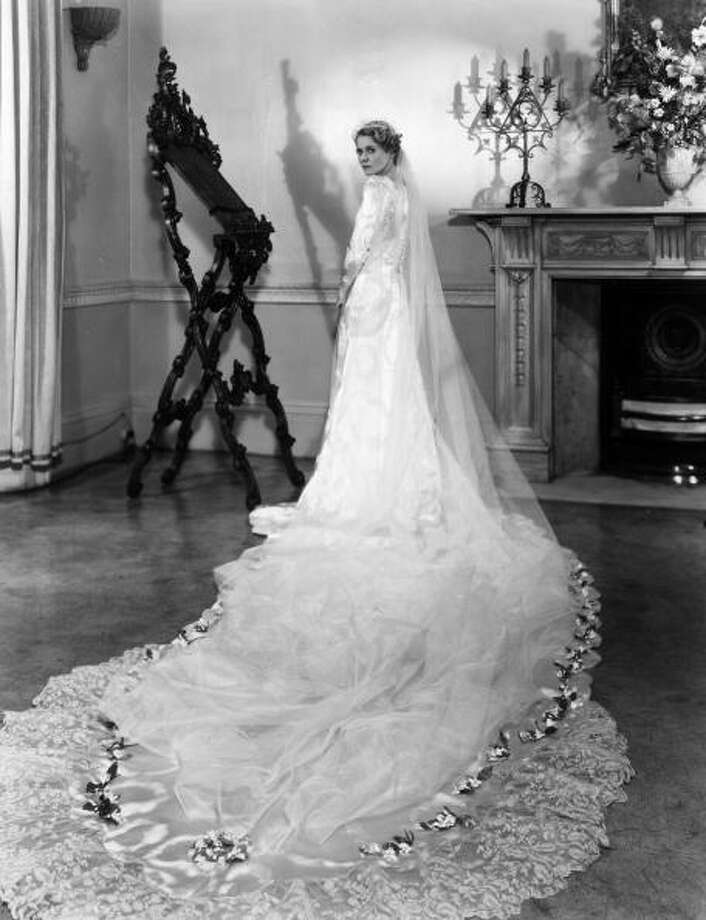 1933:Actress Ann Todd models her wedding gown. Designed and made by Helene Galin it is of white and silver damask satin with a cloud pattern. A long train is edged with lace belonging to her great great grandmother.  Photo: Sasha, Getty / Hulton Archive