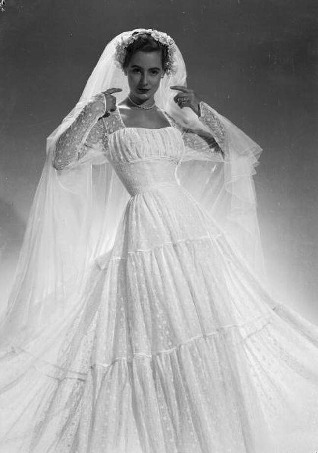 1951:  A flowing wedding dress by Mercia, with lace sleeves. Photo: Chaloner Woods, Getty / Hulton Archive