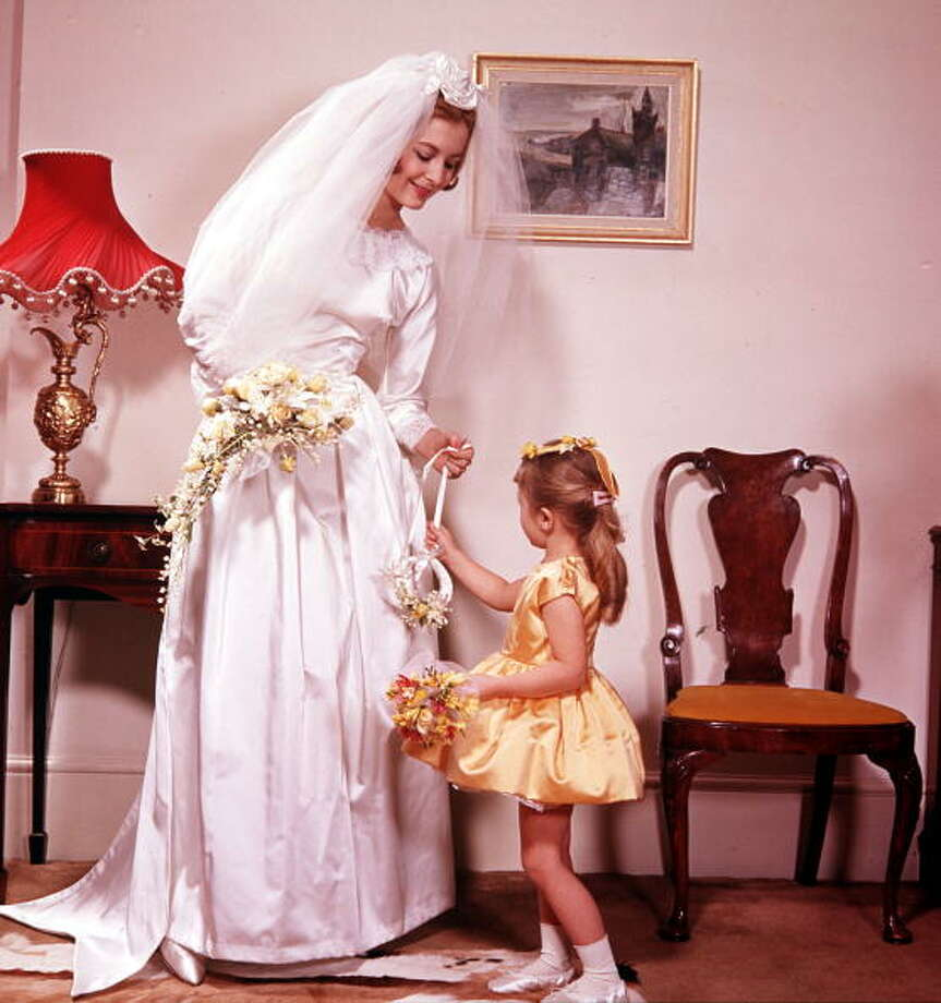 1961:A portrait of a bride with a little bridesmaid who is wearing a matching yellow dress Photo: Popperfoto, Getty / Popperfoto
