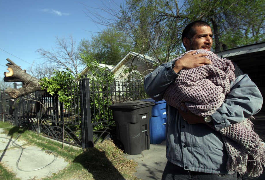 "Humberto Luna (right) holds his one-year-old son Anthony Luna while City Public Service workers restore power lines that fell early Tuesday March 5, 2013 on the 1300 block of West Theo Street near the intersection of South Zarzamora. Luna, who lives at 1335 West Theo, said he heard wind and a loud crash about 5:00 a.m. when a tree (left) fell in his yard and his power went out. ""We were pretty scared,"" Luna said. The National Weather Service expects gusts as high as 45 miles per hour this morning. Photo: JOHN DAVENPORT, San Antonio Express-News / ©San Antonio Express-News/Photo Can Be Sold to the Public"