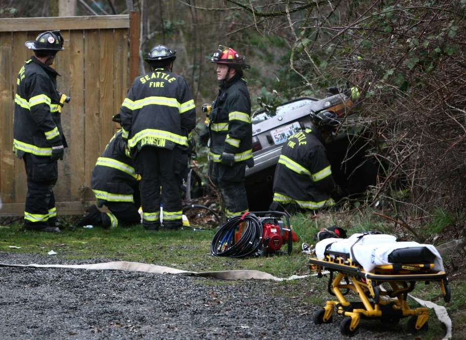 Firefighters work to remove a man that was trapped overnight in a wrecked car on the edge of a ravine on Tuesday, March 5, 2013 near Lake City Way in Seattle. The injured man was discovered under the dashboard of the wrecked vehicle by a nearby homeowner that went to investigate the accident scene. (Joshua Trujillo, seattlepi.com)