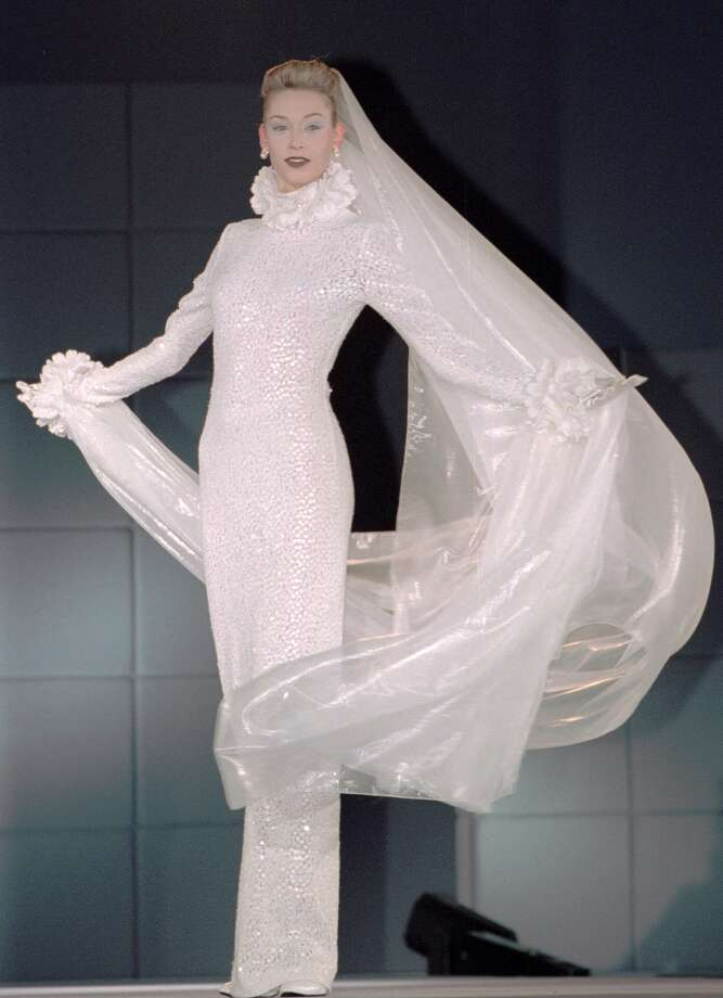 1996: A model wears a fitted wedding dress in spangle embroidered lace with a long veil Photo: ITSUO INOUYE, AP/Getty / AP