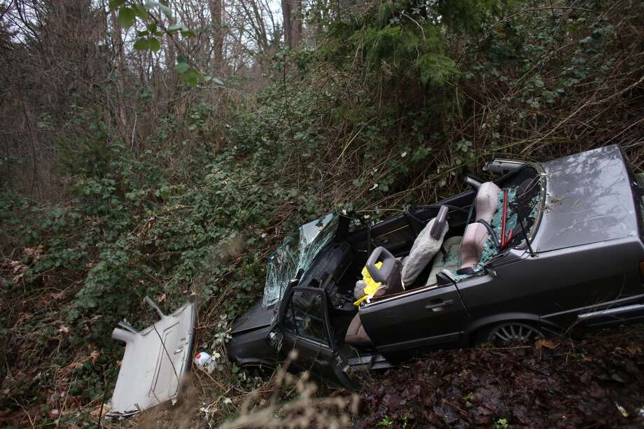 A wrecked car is shown where a man was trapped overnight on the edge of a ravine on Tuesday, March 5, 2013 near Lake City Way in Seattle. The injured man was discovered under the dashboard of the wrecked vehicle by a nearby homeowner that went to investigate the accident scene. (Joshua Trujillo, seattlepi.com)