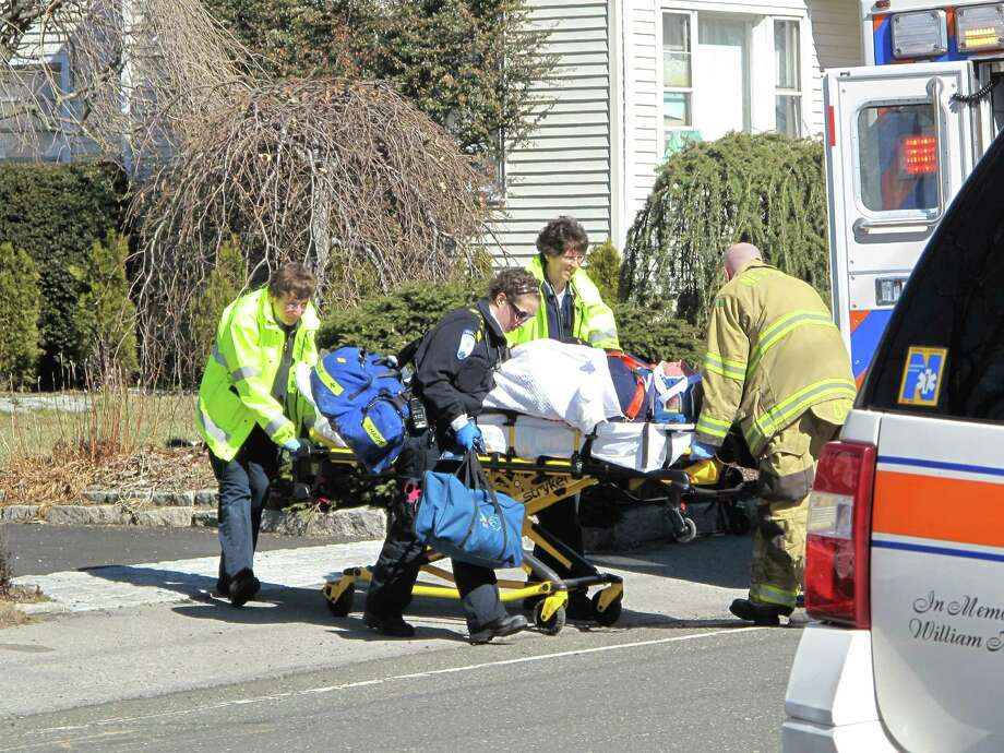Police and Emergency Services personnel transport a man into an ambulance around 1 p.m. on Tuesday, March 5 on East Avenue, New Canaan, Conn. Photo: Tyler Woods