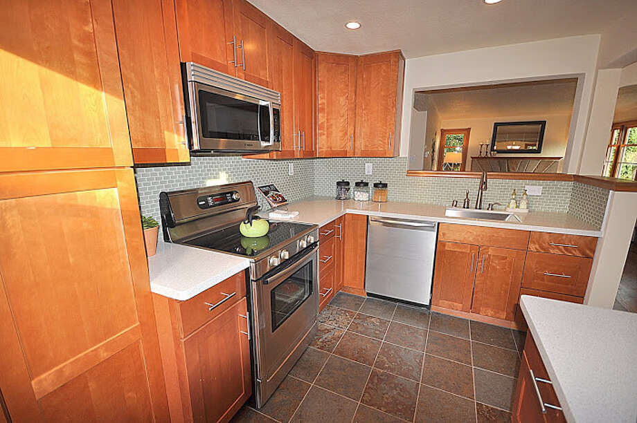 Kitchen of 830 N.E. 125th St. The 1,500-square-foot house, built in 1941, has three bedrooms, full and three-quarter bathrooms, exposed-wood moldings, a rec room and a patio on a 7,936-square-foot lot. It's listed for $389,000. Photo: Picasa, Courtesy Michael Bill And Scott Whaley/Windermere Real Estate