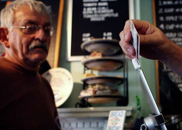 Ray Chavez watches his credit card get swiped through an iPad at W.D. Deli. The deli has used two iPads since October, saving money in credit card fees. Chavez just got an iPad as well to help with his own business. Photo: Cynthia Esparza, For The Express-News / ©2013 San Antonio Express-News