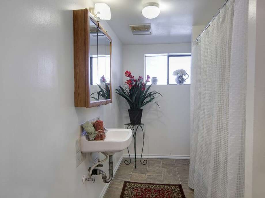 Bathroom of 12516 14th Ave. N.E. The 2,320-square-foot house, built in 1942, has three bedrooms and two bathrooms -- including a mother-in-law apartment in the basement -- a front  deck and a two-car garage on a 9,042-square-foot lot. It's listed for $349,950, although a sale is pending. Photo: Courtesy Stefanie A. Massie And Laurie Vandermay/Windermere Real Estate