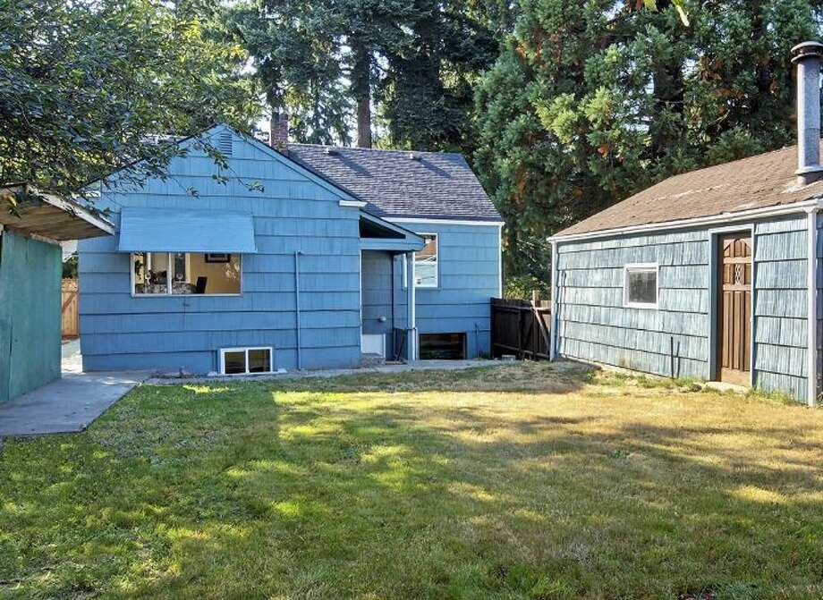 Yard of 12516 14th Ave. N.E. The 2,320-square-foot house, built in 1942, has three bedrooms and two bathrooms -- including a mother-in-law apartment in the basement -- a front  deck and a two-car garage on a 9,042-square-foot lot. It's listed for $349,950, although a sale is pending. Photo: Courtesy Stefanie A. Massie And Laurie Vandermay/Windermere Real Estate