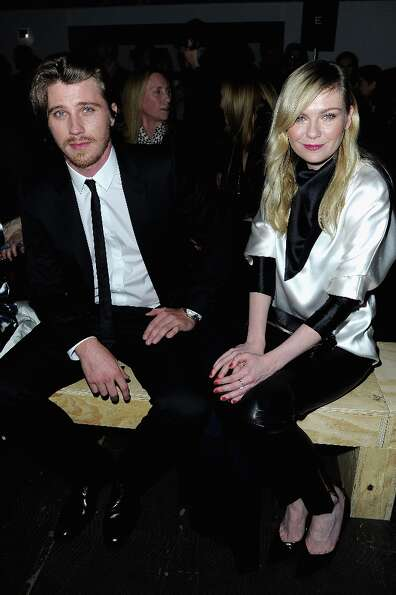 Kirsten Dunst and Garrett Hedlund attend the Saint Laurent Fall/Winter 2013 Ready-to-Wear show as pa