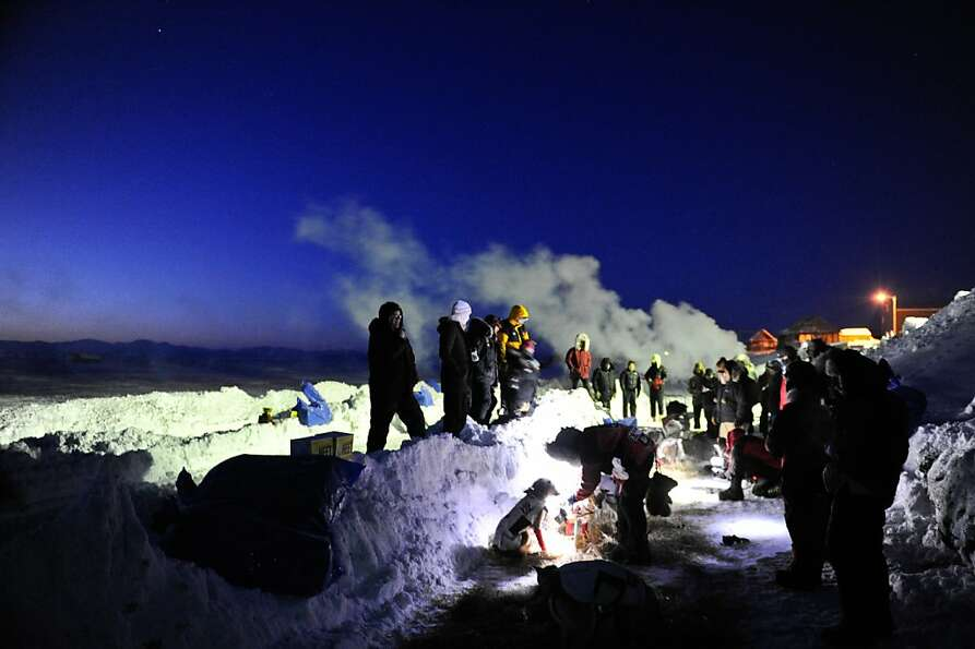 FILE - Aliy Zirkle feeds her dog team in Unalakleet, Alaska, during the Iditarod Trail Sled Dog Race