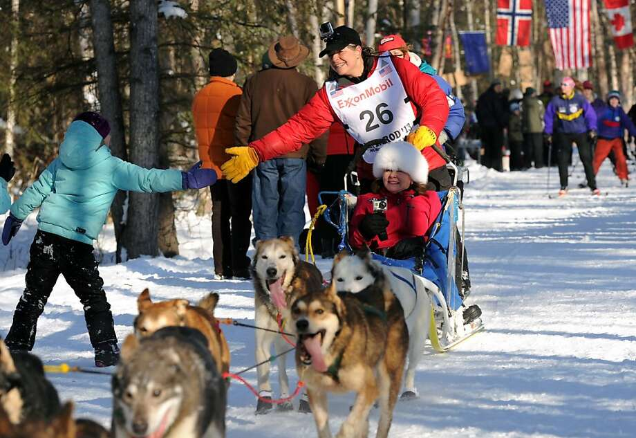 Jan Steves of Edmonds, Wash. greets a fan on the trail adjacent to Wesleyan Drive during the ceremonial start of the Iditarod Trail Sled Dog Race on Saturday, March 2, 2013, in Anchorage, Alaska. The competitive portion of the 1,000-mile race is scheduled to begin Sunday in Willow, Alaska. (AP Photo/Anchorage Daily News, Erik Hill) Photo: Erik Hill, Associated Press