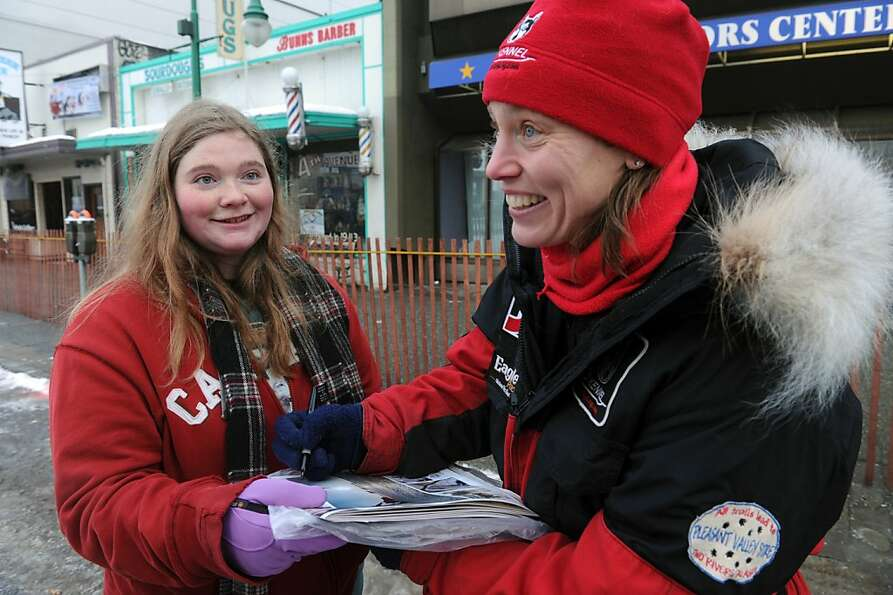 Victoria Tenney, from Seattle, collects an autograph from musher Aliy Zirkle at the ceremonial start