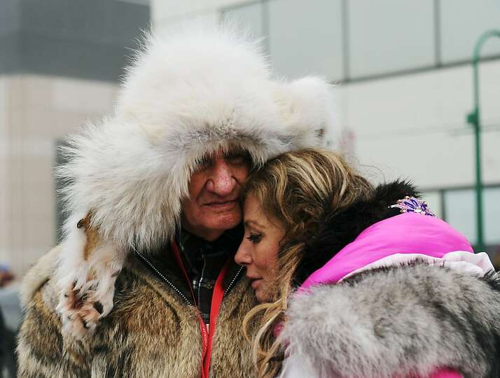 DeeDee Jonrowe rests her head on her father, Ken Stout, before the ceremonial start of the Iditarod