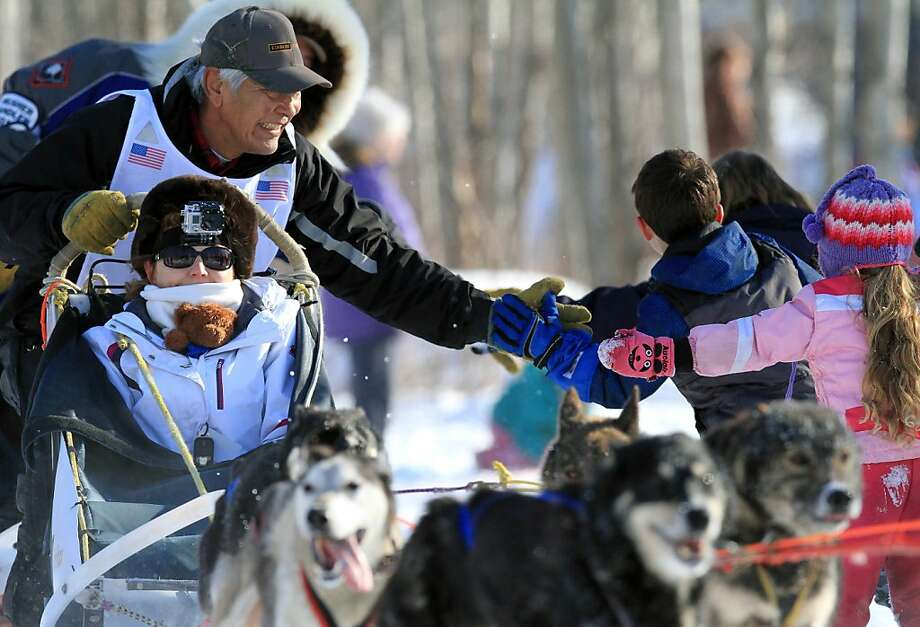 Mike Williams Sr. greets fans during the ceremonial start of the Iditarod Trail Sled Dog Race on Saturday, March 2, 2013, in Anchorage, Alaska. The competitive portion of the 1,000-mile race is scheduled to begin Sunday in Willow, Alaska. (AP Photo/Dan Joling) Photo: Dan Joling, Associated Press